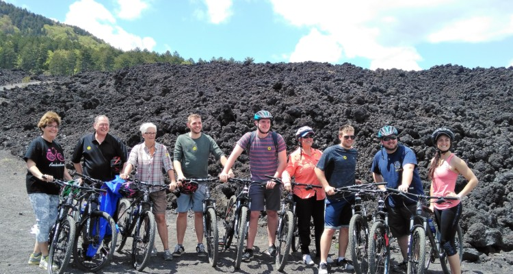 A bunch of new mtbikers riding on Mount Etna's lava flow